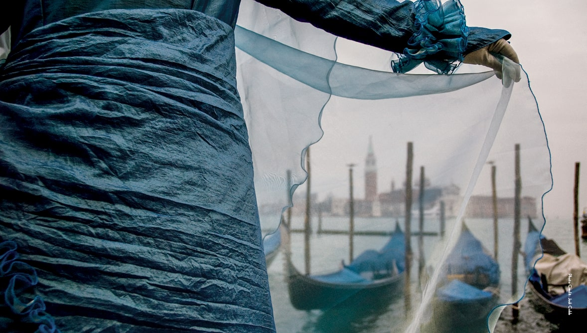 Image of Venetian gondolas seen through woman's thin blue veil
