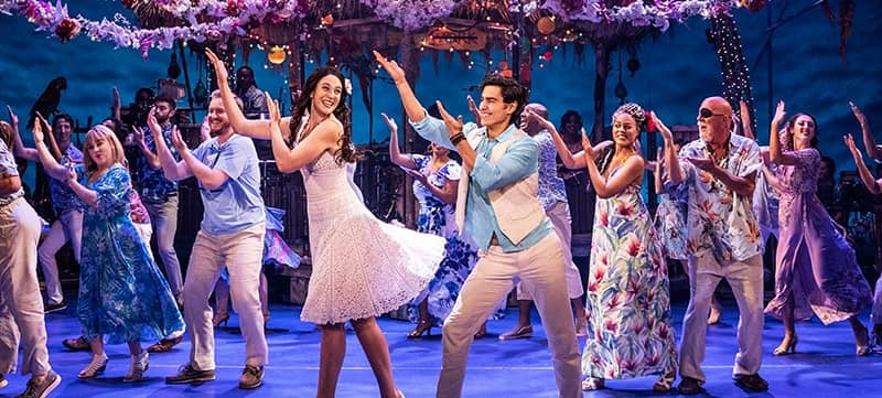 "Image of cast members from Jimmy Buffett's ""Escape to Margaritaville"" on stage"