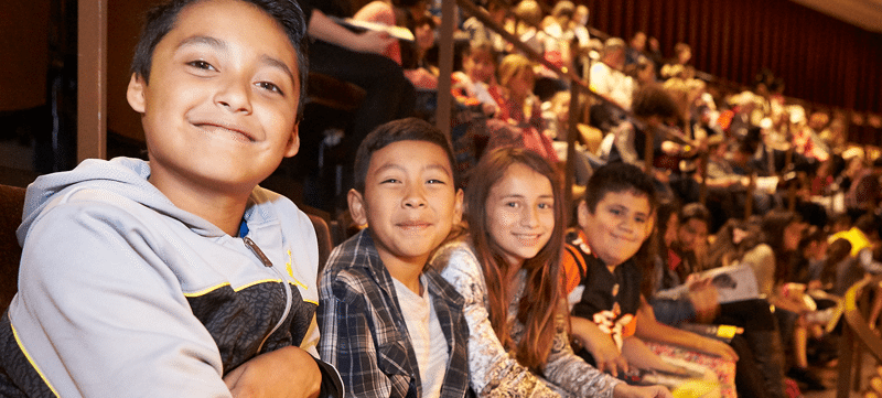 Smiling school children in the Reynolds Hall balcony at a student matinee performance