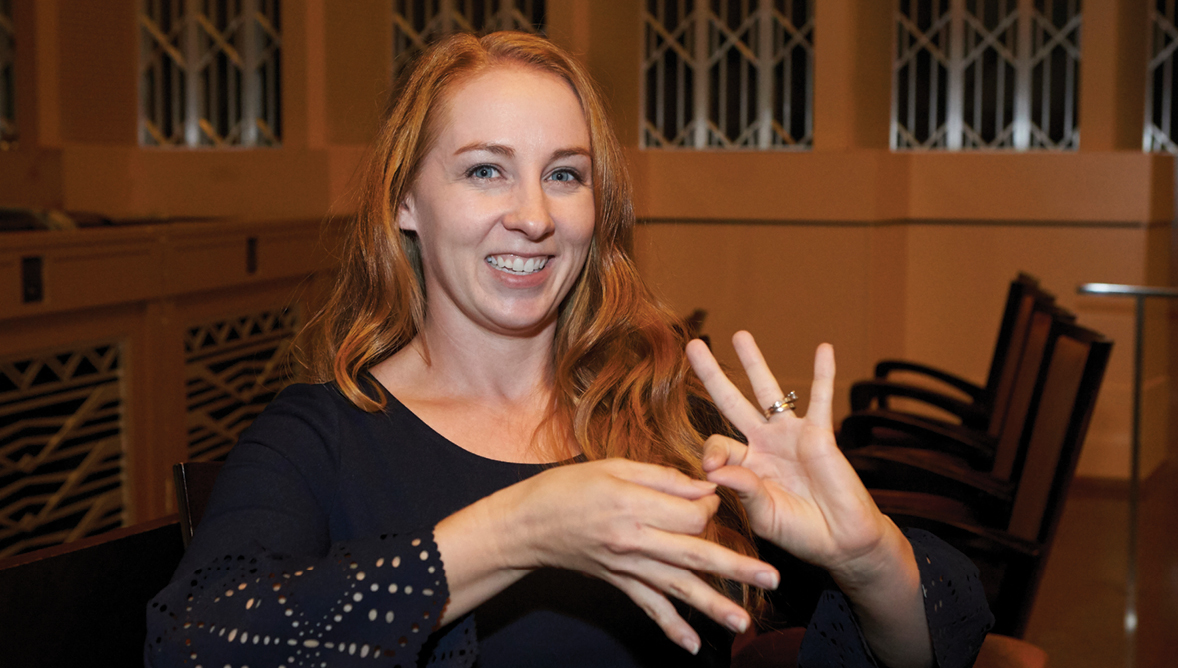 A photo of a woman doing sign language.