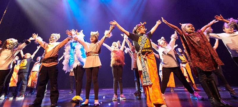 Image of students on the Reynolds Hall stage performing with Disney Musicals in Schools