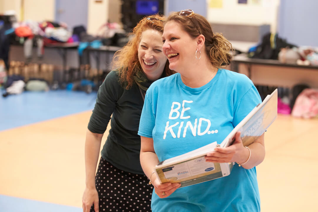 A photo of teachers laughing during a workshop with a teaching artist
