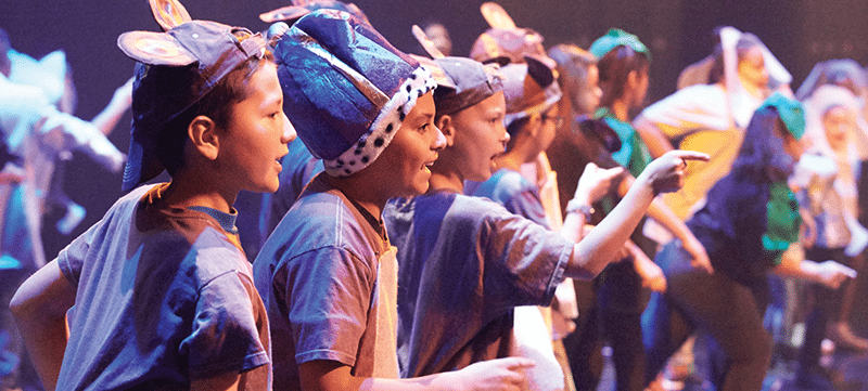 Young students on stage in a Disney Musicals in Schools production