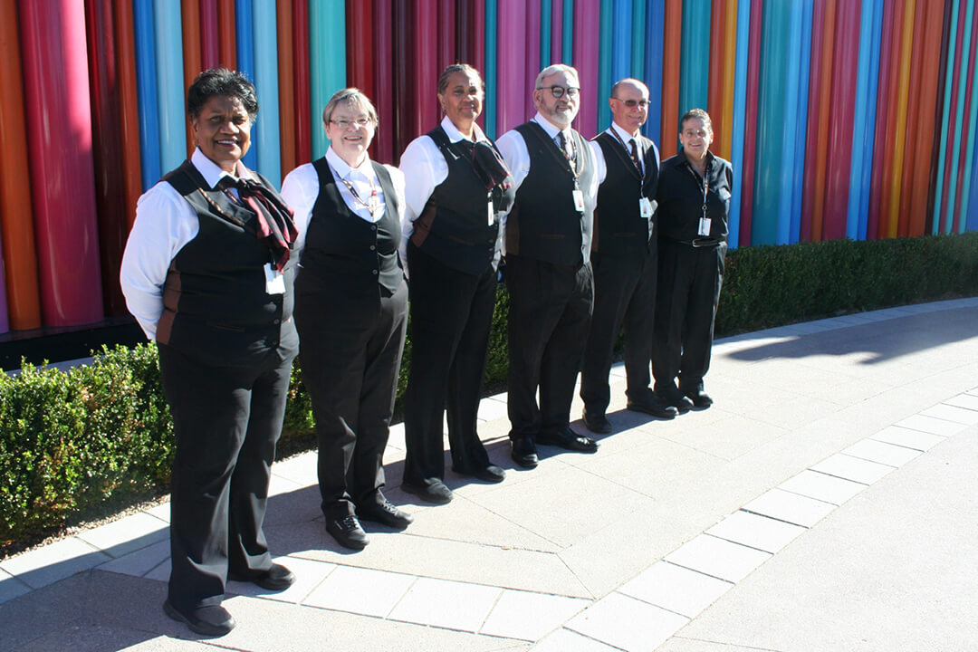 A photo of volunteers smiling and standing in a group while wearing uniforms.