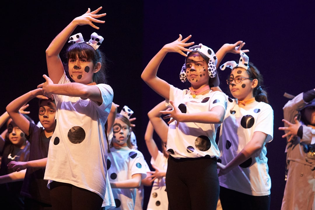 A photo of elementary students performing in costume Disney's One Hundred and One Dalmatians Jr. on stage in Reynolds Hall at The Smith Center.