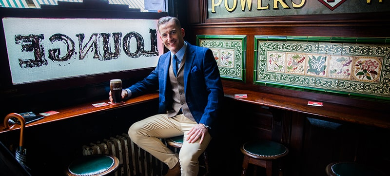 Paul Byrom in an Irish pub drinking a Guinness