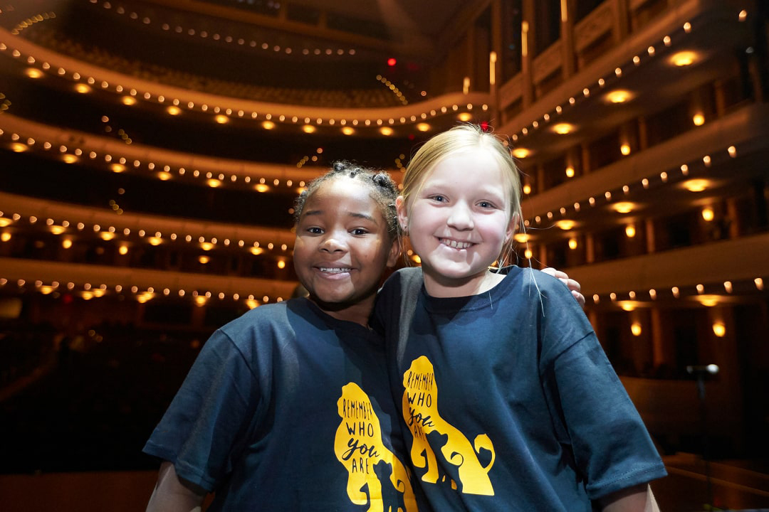 A photo of elementary students in their cast shirts on The Smith Center stage before performing a song from their school musical, Disney's The Lion King Jr.
