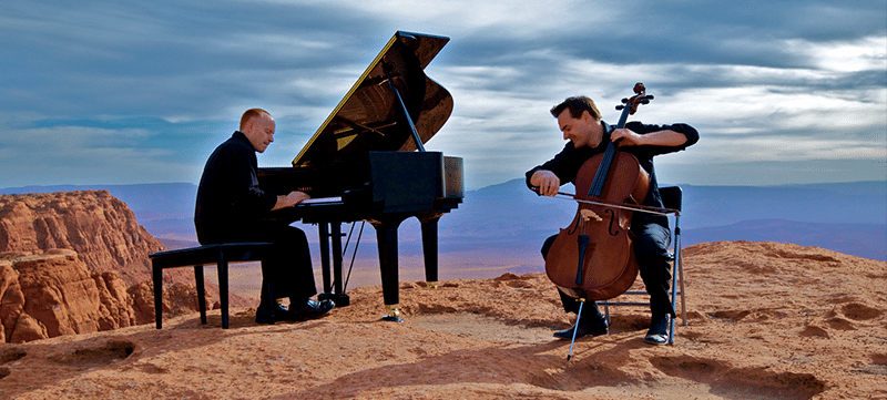 The Piano Guys performing overlooking a desert canyon