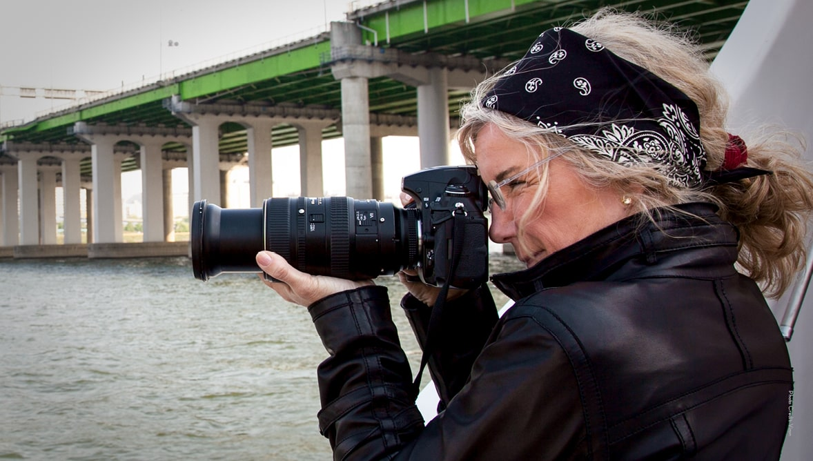 Image of photojournalist Jodi Cobb with a camera in front of a bridge