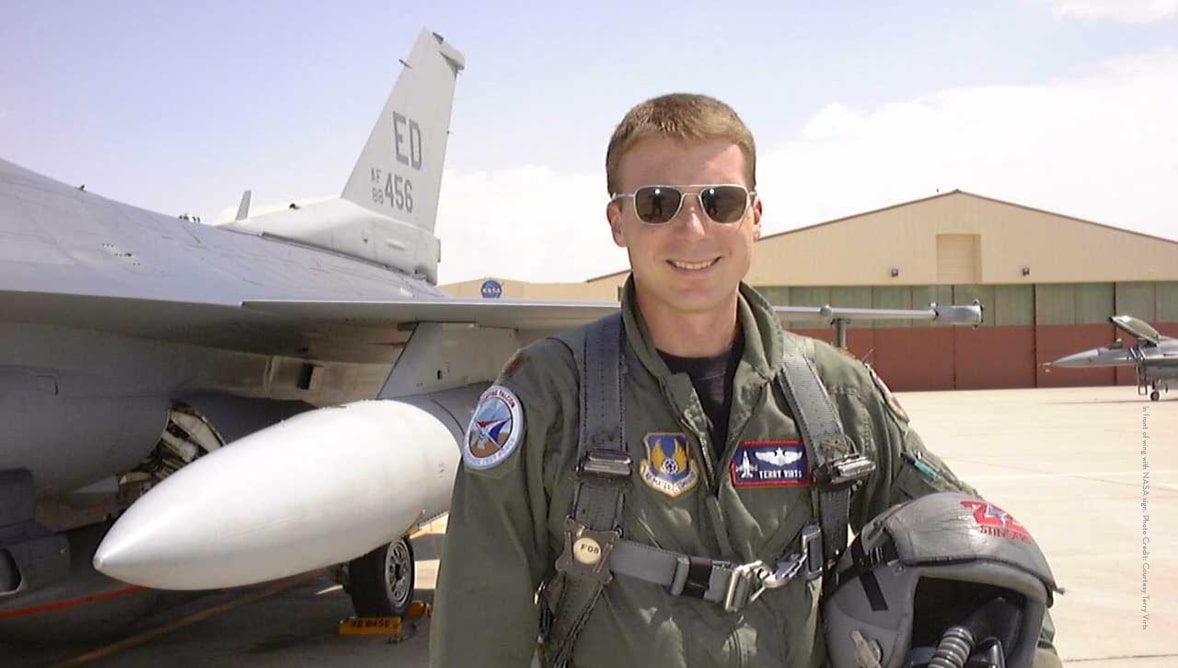 Image of Terry Virts in a flight suit in front of a fighter jet