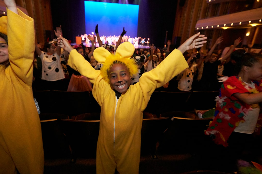 A photo of an elementary student in costume a Simba with other students in costume in the background in seats and on stage in Reynolds Hall.