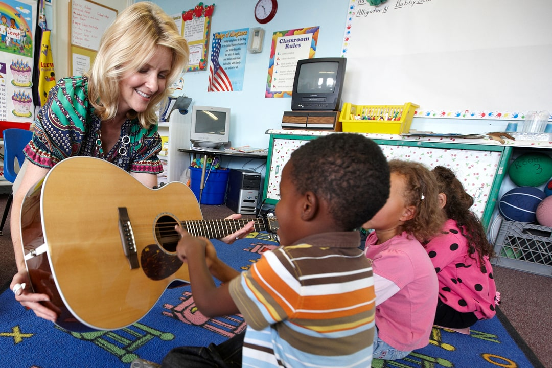 A Smith Center teaching artist showing students a guitar in their classroom