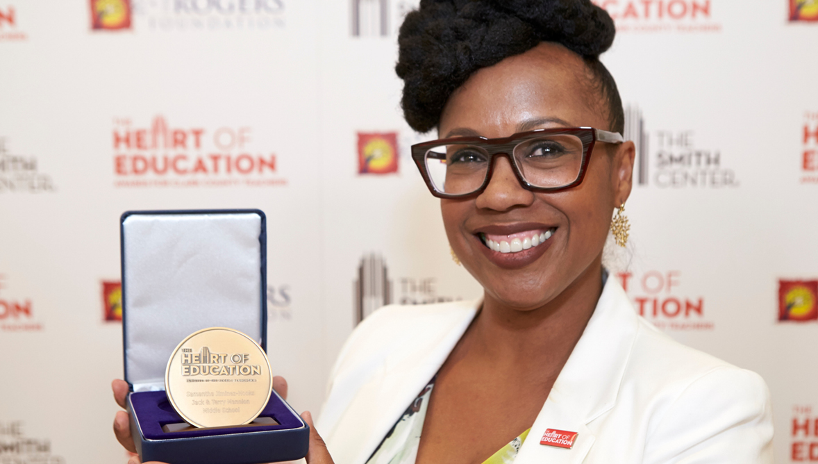 A photo of a Heart of Education award winner holding their medallion.