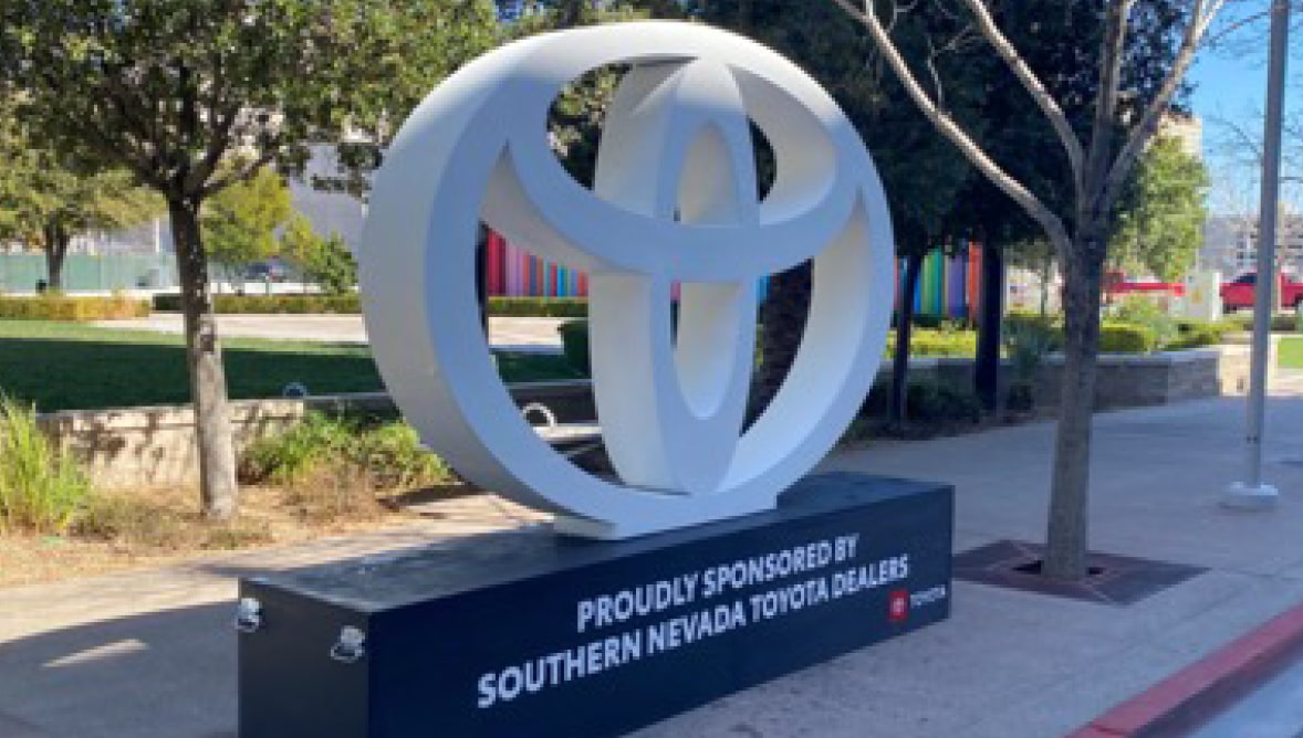 A photo of a sponsor logo sculpture in front of The Smith Center