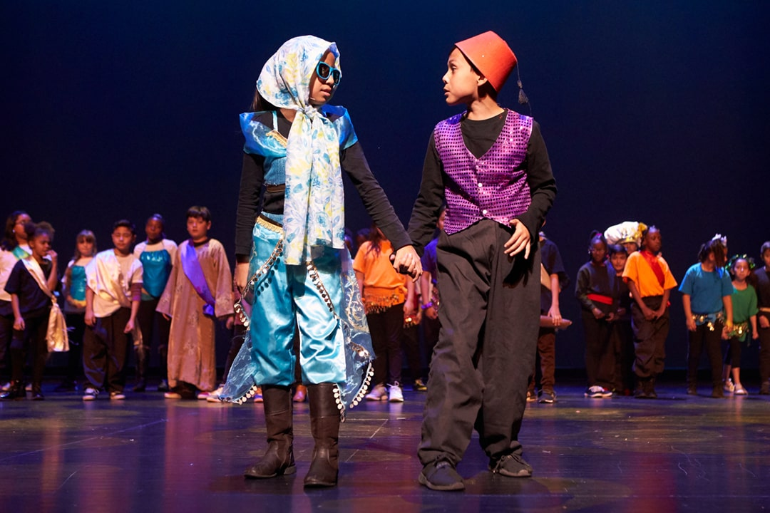 A photo of elementary students performing as Aladdin and Jasmine from Disney's Aladdin Jr. with a chorus of students in the background on stage in Reynolds Hall at The Smith Center.