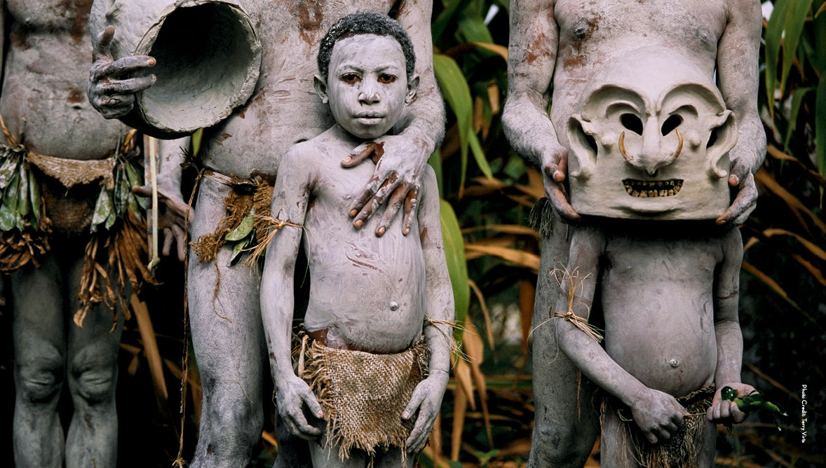 Young boys and men in tribal makeup and clothing in Papua New Guinea