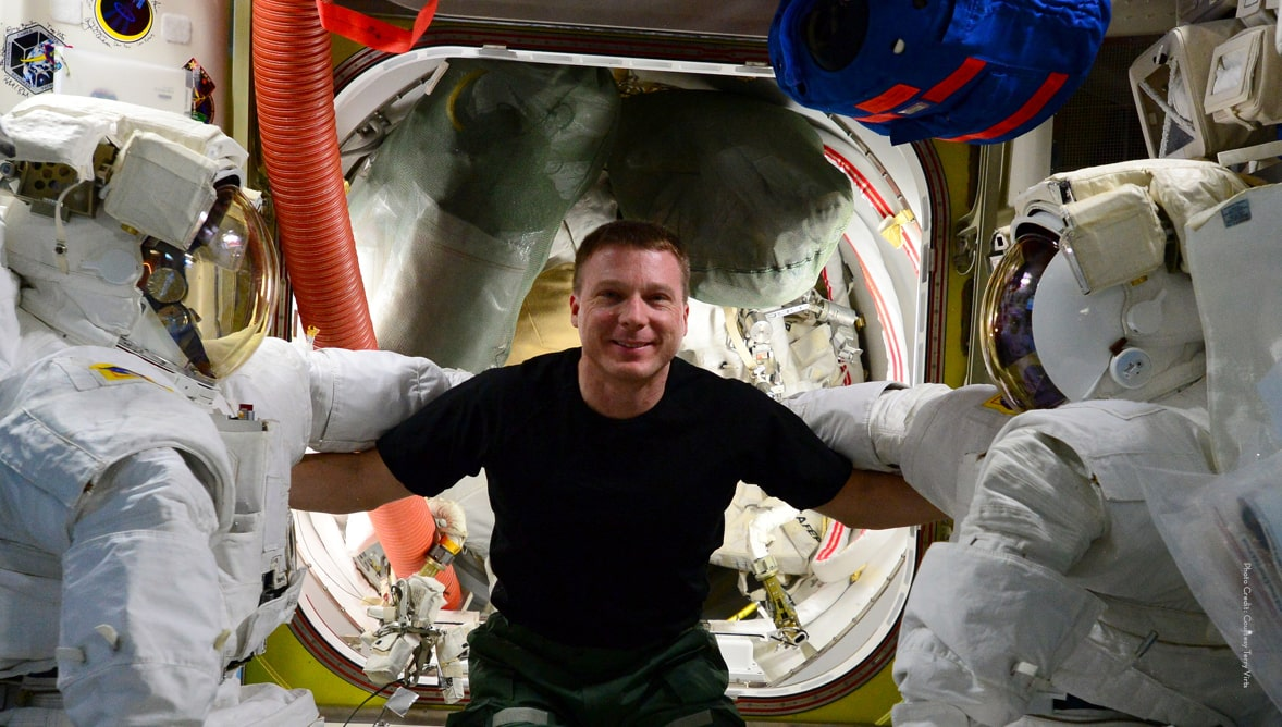 Image of Terry Virts in the international space station linking arms with two space suits